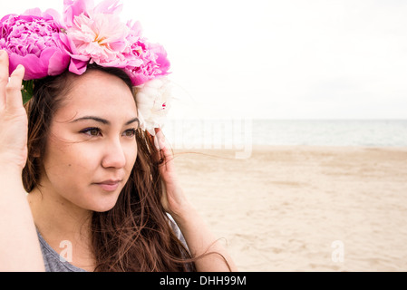 Young woman on beach with flowers in her hair