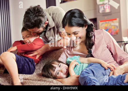 Family with two children playing on sofa - Stock Photo