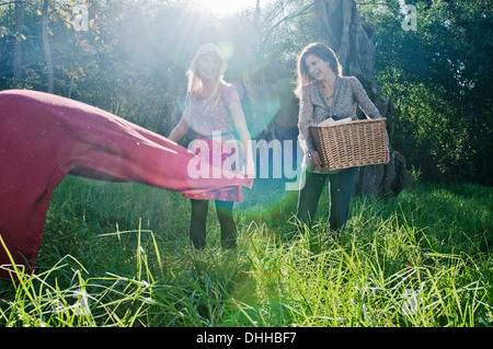Young women laying out picnic blanket - Stock Photo