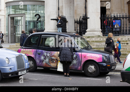 A woman Hiring a Famous Black Cab in London England - Stock Photo