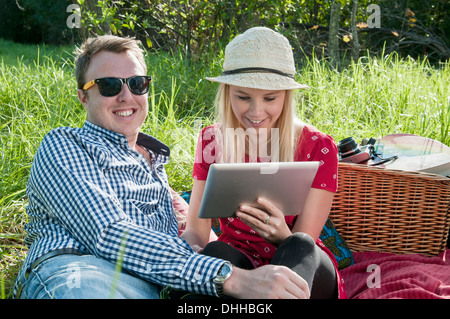 Young couple sitting on picnic blanket using digital tablet - Stock Photo