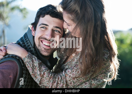 Young woman hugging boyfriend - Stock Photo