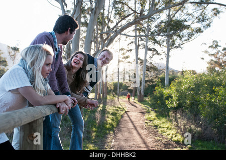 Group of four friends leaning on fence - Stock Photo