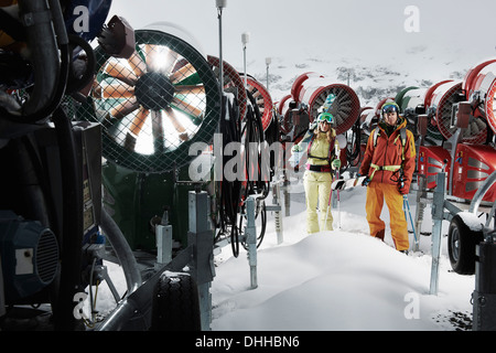 Young people standing among snowmobiles - Stock Photo