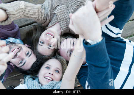 Group of four friends with heads together - Stock Photo