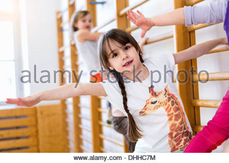 Girls climbing on gym apparatus, arm open stretching - Stock Photo
