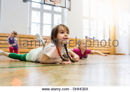 Girls lying on front in physical education class, stretching - Stock Photo