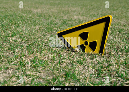 Berlin-Mitte, Germany. 01st April, 2011. ILLUSTRATION A radioactivity warning sign sticks out of a lawn in Berlin - Stock Photo