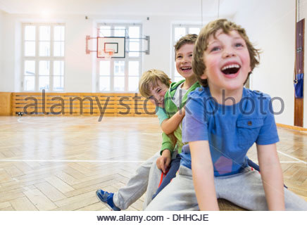 Boys sitting on bench in school hall, laughing - Stock Photo