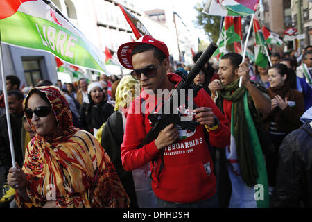 Madrid, Spain. 09th Nov, 2013. People from Western Sahara shout slogans as they wave Western Sahara's flags in support - Stock Photo