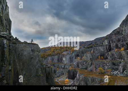 Freestyle cyclist on top of cliff, Llanberis, North Wales, UK - Stock Photo