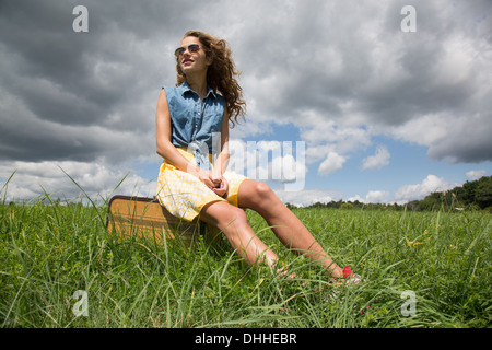 Teenage girl sitting on suitcase in field - Stock Photo