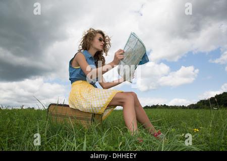 Teenage girl sitting on suitcase reading map - Stock Photo