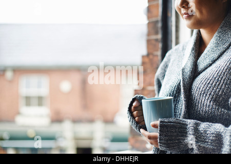Young woman in kitchen holding mug of coffee - Stock Photo