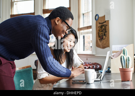 Young couple using laptop at home - Stock Photo