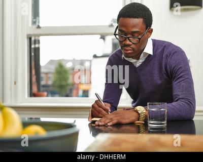 Young man making notes at kitchen counter