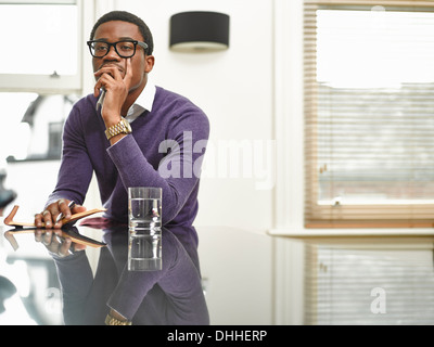 Young man with notebook on kitchen counter - Stock Photo