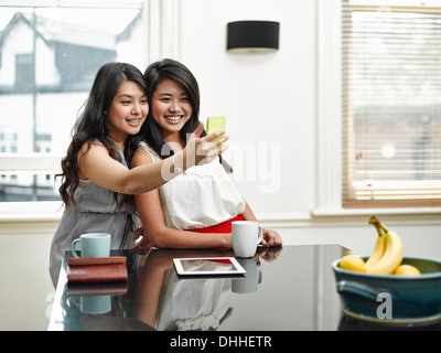 Two young women taking self portrait in kitchen - Stock Photo