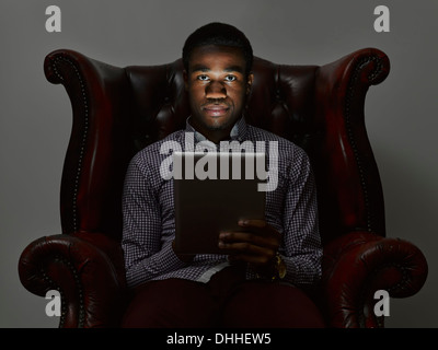 Portrait of sinister young man in armchair with digital tablet - Stock Photo