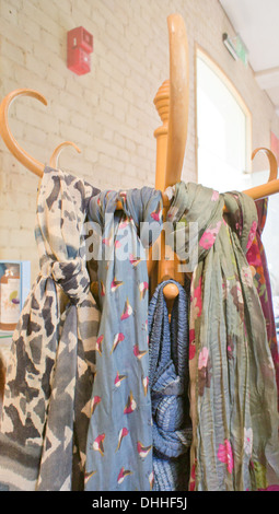 Ladies' scarves hanging on a wooden stand in a shop - Stock Photo