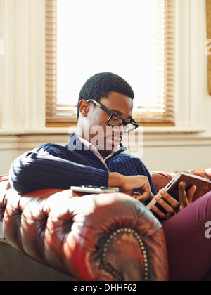 Young man reading on sofa - Stock Photo