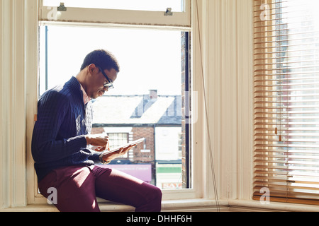 Young man reading on windowsill - Stock Photo