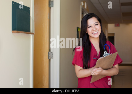 Portrait of young female nurse with clipboard - Stock Photo