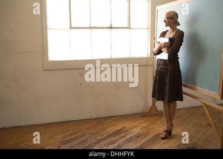 Teacher looking out of window - Stock Photo