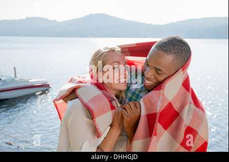 Young couple wrapped in blanket by lake, Hadley, New York, USA - Stock Photo