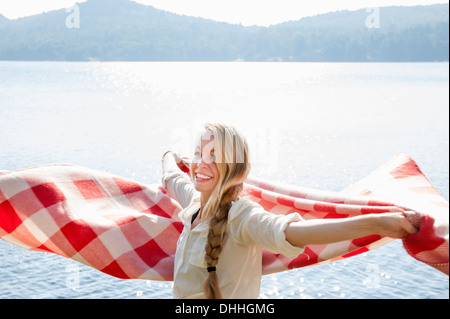 Young woman holding blanket by lake, Hadley, New York, USA - Stock Photo