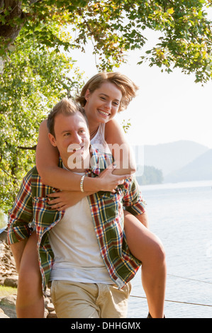 Young man giving woman piggy back - Stock Photo