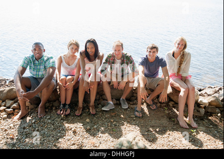 Portrait of friends sitting on stone wall - Stock Photo