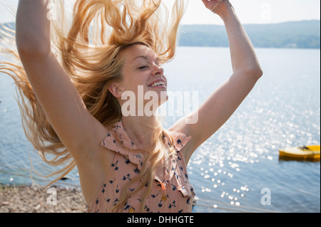 Portrait of young woman with long blonde hair and arms raised - Stock Photo