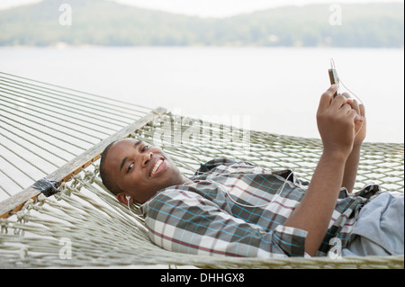 Young man lying on hammock listening to music - Stock Photo