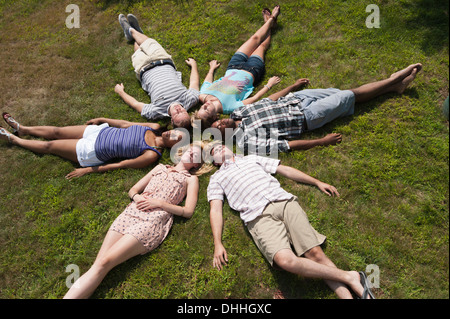 Friends lying on grass asleep in circle - Stock Photo