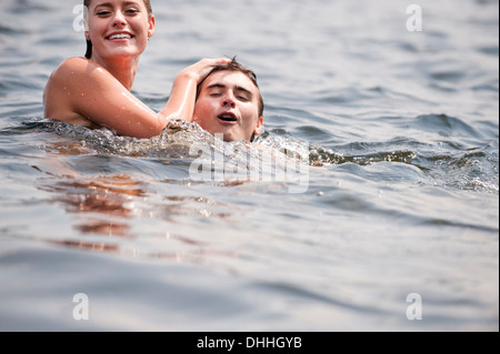 Young couple swimming in lake - Stock Photo