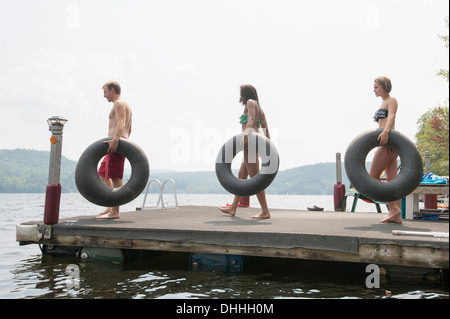 Friends on jetty carrying inflatable rings - Stock Photo