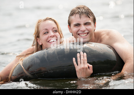 Young couple floating in inflatable ring - Stock Photo