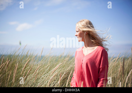 Portrait of blonde woman wearing pink sweater in marram grass, Wales, UK - Stock Photo