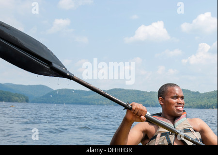 Young man wearing life vest holding oar - Stock Photo