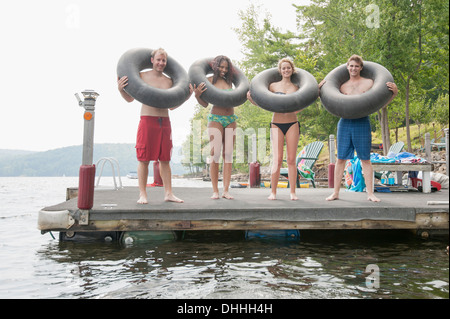 Friends on jetty with inflatable rings around necks - Stock Photo