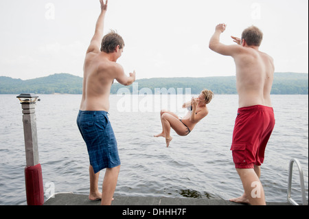 Men throwing young woman off jetty into lake - Stock Photo
