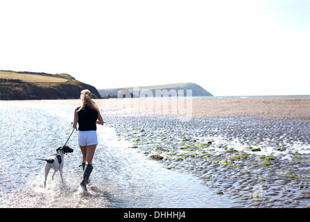 Woman walking dog on beach, Wales, UK - Stock Photo