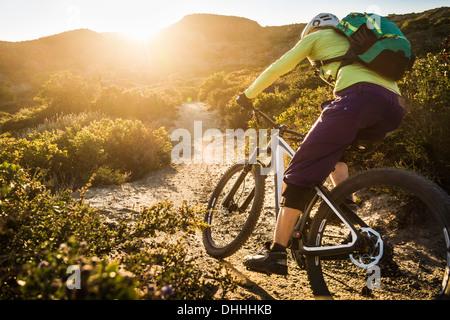 Young woman mountain biking on dirt track, Monterey, California, USA