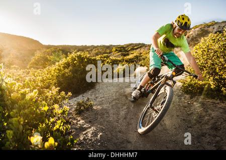 Young man mountain biking on dirt track, Monterey, California, USA - Stock Photo