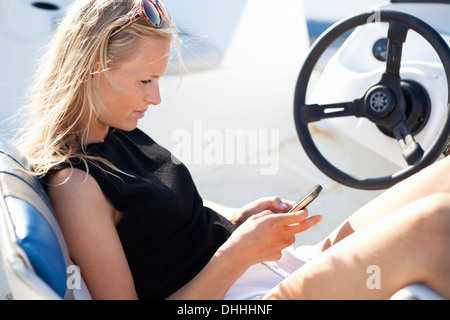 Woman using cell phone in yacht, Wales, UK - Stock Photo