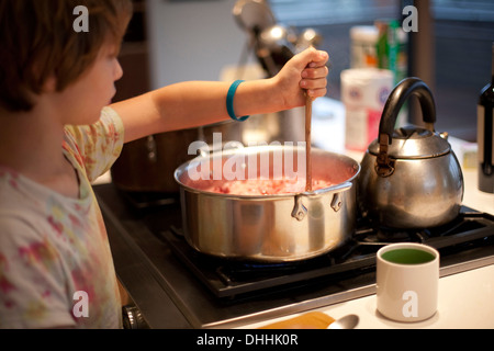 Boy stirring pan of food on stove - Stock Photo