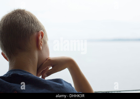 Rear view of boy looking out of window - Stock Photo