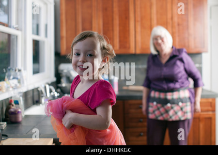 Girl and grandmother standing in kitchen - Stock Photo