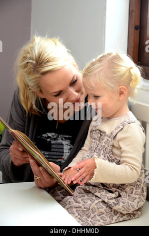 Mother reading a book with her little daughter, Sweden - Stock Photo